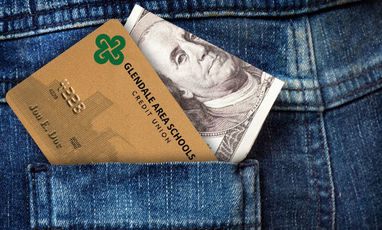 The back pocket of a pair of jeans with a credit card and cash poking out of it
